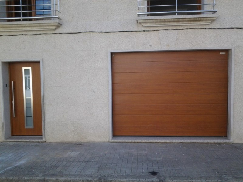 Puerta Seccional y puerta de entrada a juego con rotura de puente térmico y acústico en acabado SILGRAIN GOLDEN OAK