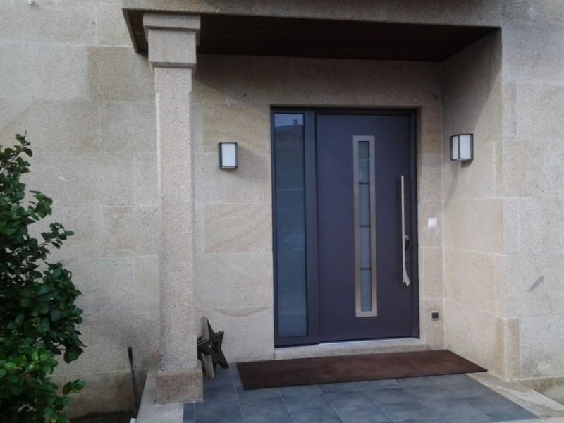 Puerta de entrada con fijo lateral acristalado. Todo el conjunto, incluido marco, con rotura de puente térmico (aislante térmico) y aislante acústico