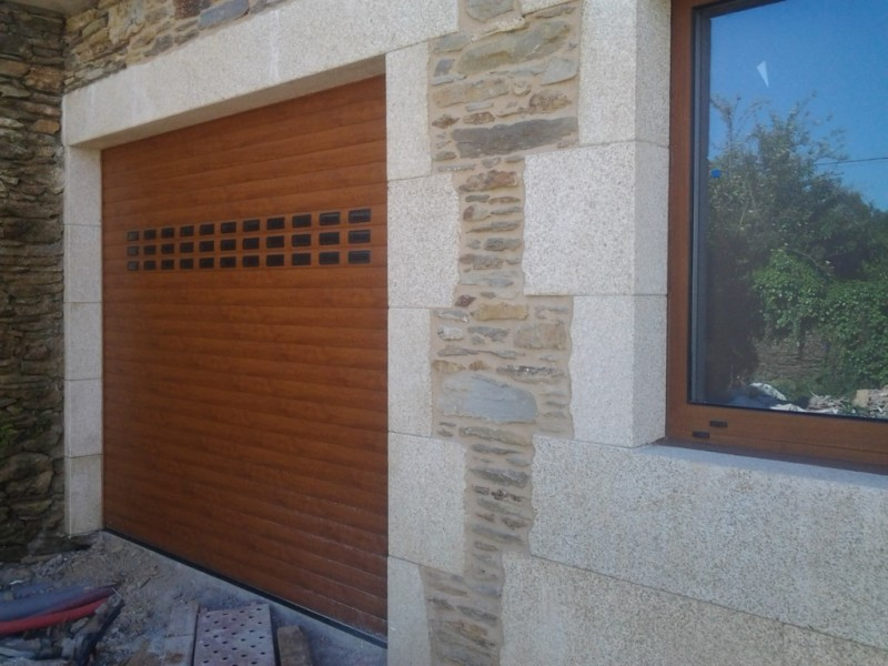 Puerta enrollable aislante, con visores transparentes y acabado GOLDEN OAK