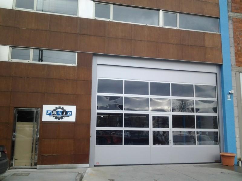 Puerta industrial acristalada con puerta peatonal, sin galce, y cámara de policarbonato de 26mm