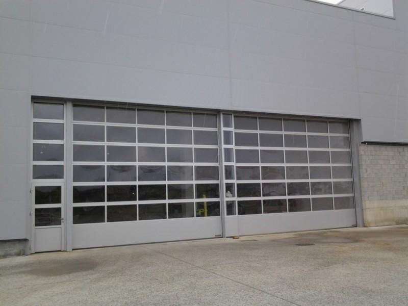 Puertas acristaladas de 8 metros de ancho con puerta peatonal lateral y fijo superior a juego