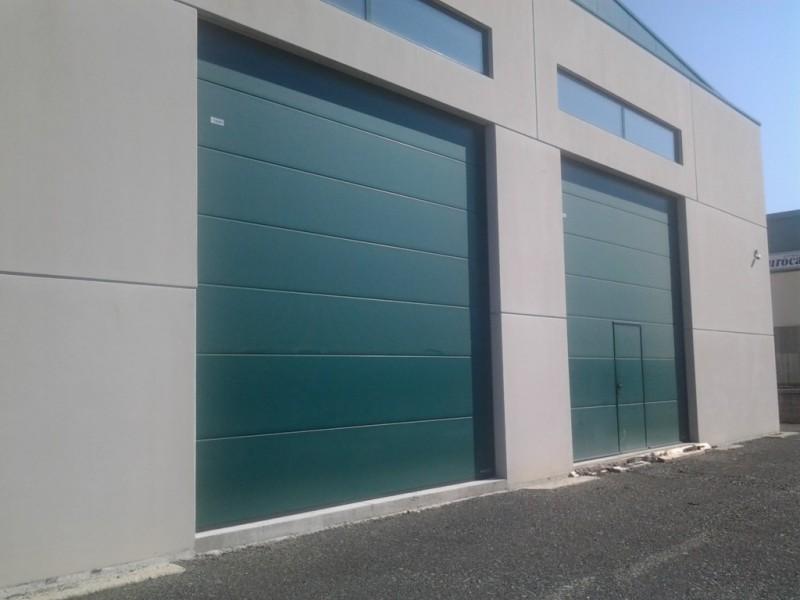 Puertas industriales con puerta peatonal incorporada en acabado MICROGRAIN